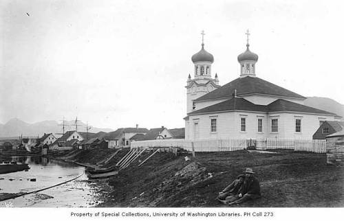 Two men seated on shore in front of Russian Orthodox church, Unalaska, ca. 1899
